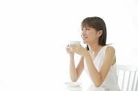 ティータイムを楽しむ白いワンピースの若い日本人女性