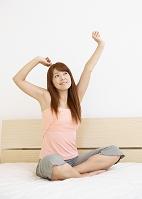 ベッドの上で伸びをするミドルの女性