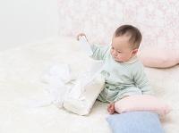 座ってティッシュペーパーを持つ日本人の赤ちゃん
