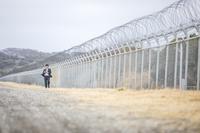 フェンス横を歩く日本人ビジネスマン