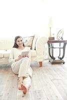 ソファを背もたれにタブレットを楽しむ若い日本人女性