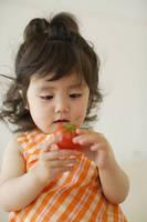 トマトを持つ幼い女の子