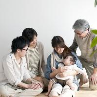 赤ちゃんを囲み団らんする3世代日本人家族