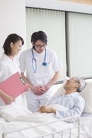 ベッドの入院シニア患者を診察する医者と看護師