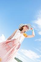 青空の下に立っているサングラスをかけた日本人女性