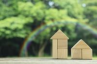 森の中に置かれた積み木の家と虹