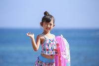 海で浮き輪をもって手をふる少女