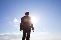太陽と向き合うビジネスマン
