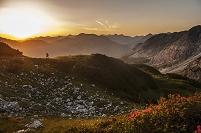 オーストリア 夜明けの山を登る男性