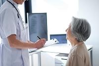男性医師から問診されるシニア女性