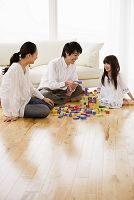 両親と積み木で遊ぶ子供