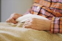 ベッドで横になる女性の手