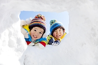 雪の公園で穴をのぞき込む兄弟