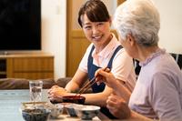 シニアの食事につきそう日本人女性ヘルパー