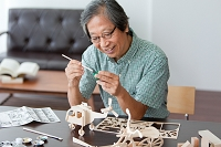 模型に色を塗る中高年男性