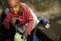 ウガンダ ボトルに水をくむ少年
