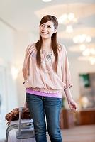 スーツケースを持つ笑顔の日本人女性