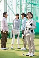 ゴルフクラブを持つ熟年女性と家族