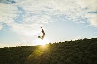 日の出をバックにジャンプする若者