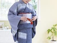 着物の帯紐を結ぶ日本人のシニア女性