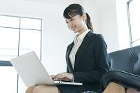 膝の上でパソコンを操作するスーツ姿の若い女性の横顔