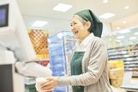スーパーのレジで働くシニア日本人女性