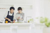 キッチンに並んで料理する日本人夫婦