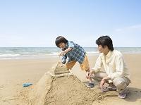 浜辺で砂遊びをする父と子