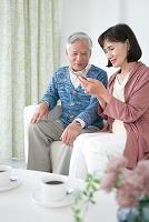 スマートフォンを見て話すシニア夫婦