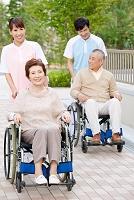 介護士と車いすに乗った中高年男女