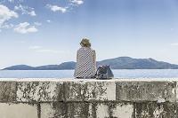 海辺で腰を下ろす女性の後ろ姿