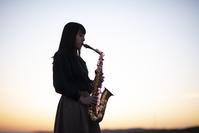 夕景の中でサックスを演奏する日本人女性