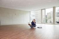 空っぽの部屋で考えごとをする女性