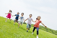 公園を手を繋いで走る小学生