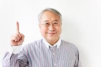 人差し指を立てるシニアの日本人男性