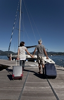 ボートまで荷物を運ぶ中年カップル