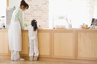 キッチンに立つエプロン姿の母と娘の後ろ姿