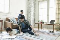 部屋でくつろぐ若い夫婦と日本人の子供