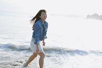 波打ち際ではしゃぐ若い日本人女性