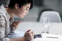 スマートフォンを見ながら食事する女性