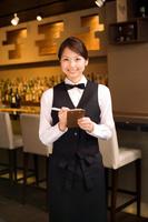 伝票にメモする日本人女性従業員