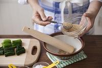 胡麻をすり鉢に入れる女性