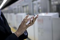 地下鉄のホームでスマートフォンを操作するビジネス女性