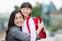 女の子を抱き締める母親