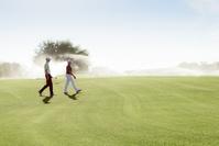友人とゴルフコースを回る男性