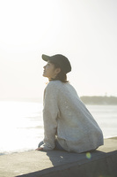 海沿いに座る笑顔の20代女性