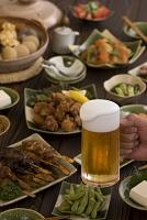 ビールジョッキを持つ手と居酒屋料理