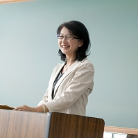 黒板の前に立ち授業をする日本人女性教師