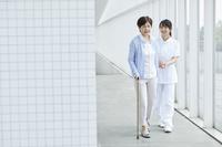 廊下を歩く日本人のシニア女性と介護士