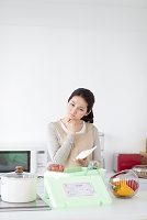 電卓を持って悩む日本人女性